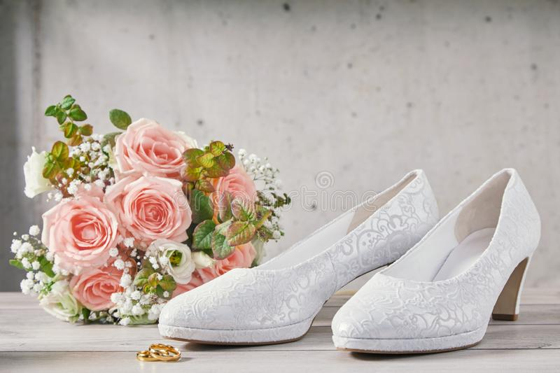 Bouquet of pink roses next to wedding shoes stock photos