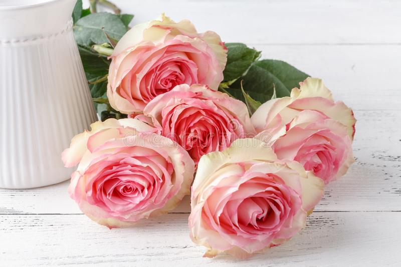 Bouquet of pink roses on old wooden board background, vintage to stock photo