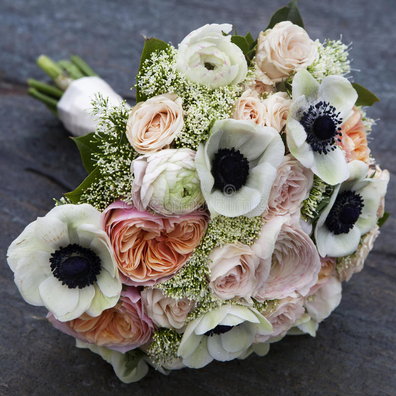 Bouquet of pink roses and white anemone and pink ranunculus. Wedding bouquet of pink roses and white anemone and pink ranunculus lying on wooden floor royalty free stock images