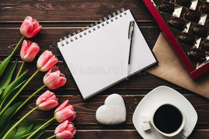Bouquet of pink Tulip flowers and a Cup of coffee with a box of sweet chocolates on the wooden table stock photos
