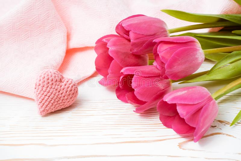 Bouquet of pink tulips and a knitted heart on a table royalty free stock images