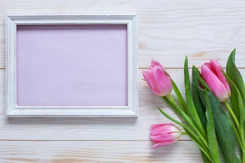 Bouquet of pink tulips and place for text in wooden white frame. Top view, close-up, flat lay on white wooden background royalty free stock images