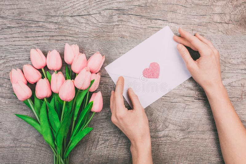 A bouquet of pink tulips and women`s hands are holding a blank envelope with a heart, on a wooden background. stock photography