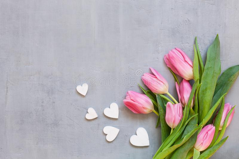 Bouquet of pink tulips and wooden hearts pattern. Concept for Valentine`s Day, womens day and other romantic events. Top view, stock photo