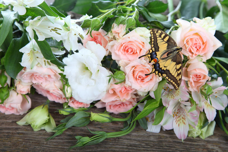Bouquet of pink and white flowers. And butterfly on a wooden background stock images