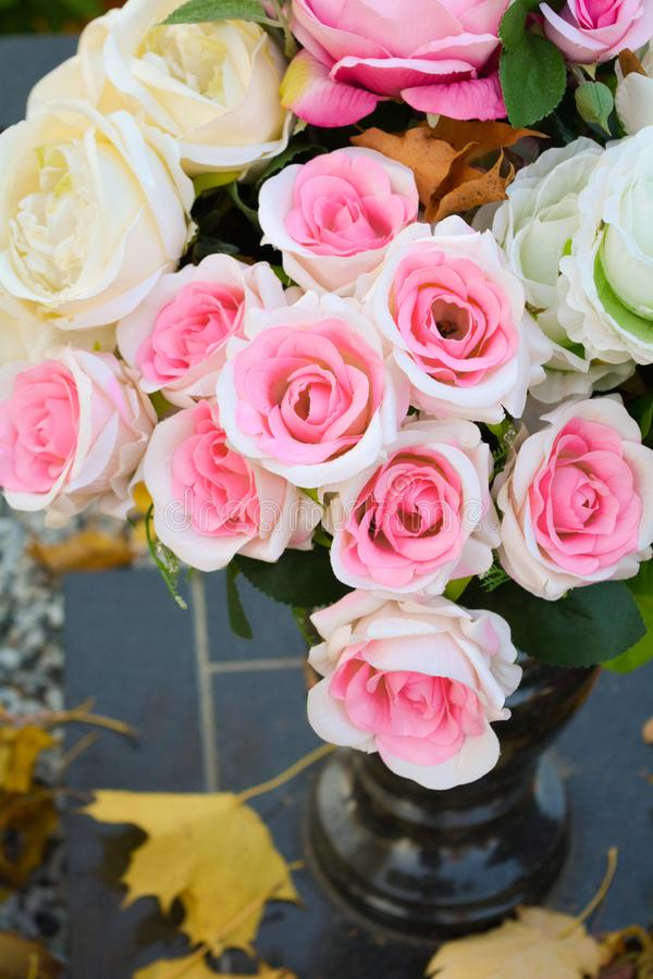 Bouquet of pink and white rose flowers, autumn fallen leaves on ground royalty free stock image