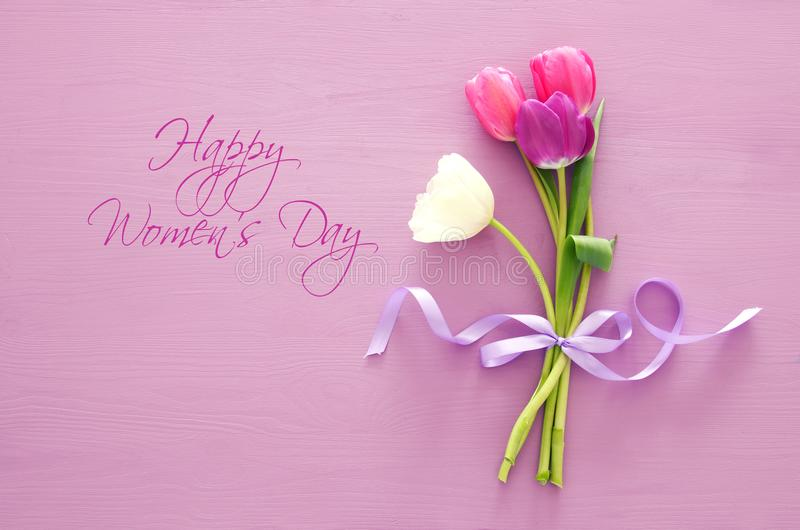 bouquet of pink and white tulips over pastel wooden background. Top view. International women day concept. stock photo