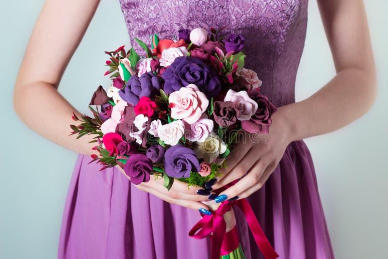 Bouquet pour la jeune mariée, fille dans la robe de soirée pourpre jugeant un grand bouquet des roses multicolores disponible photo libre de droits