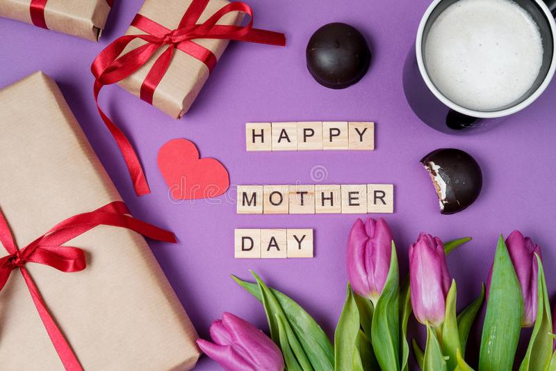 Bouquet of purple tulips, gift box and wood letters on violet ba stock image