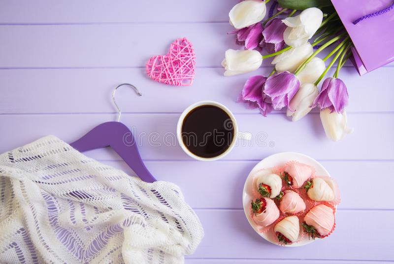 Bouquet of purple and white tulips, cup of coffee, strawberry in chocolate, pink wicker heart and hanger with clothes on lilac. Wooden background. Spring royalty free stock photo