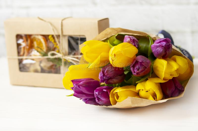 A bouquet of purple yellow tulips with handmade sweets gifts. Candy and flowers as a gift to a woman stock photo