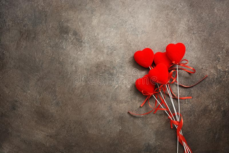 Bouquet of red hearts on a dark brown background. Valentine`s Day. Top view, flat lay, copy space stock image