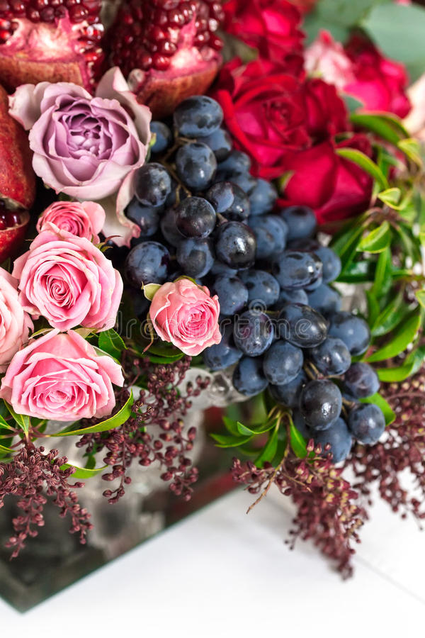 A bouquet of red and pink roses, peonies with grapes and pomegranate closeup stock photography