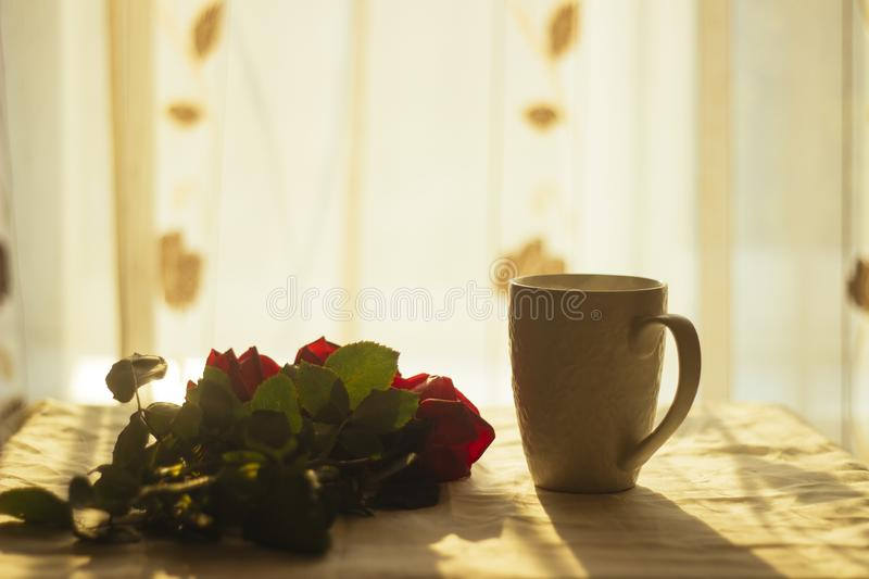 Bouquet of red roses on a background with a mug of hot tea. royalty free stock images