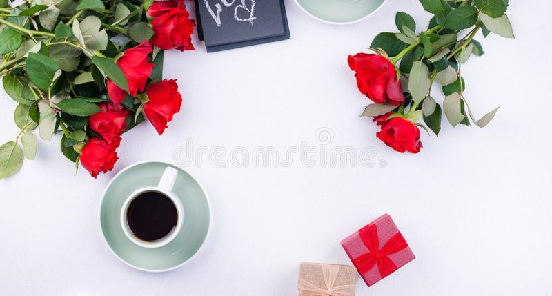 A bouquet of red roses and fresh aromatic tea for a romantic breakfast. Flowers and a letter as a gift. Valentine`s day and mothe royalty free stock images