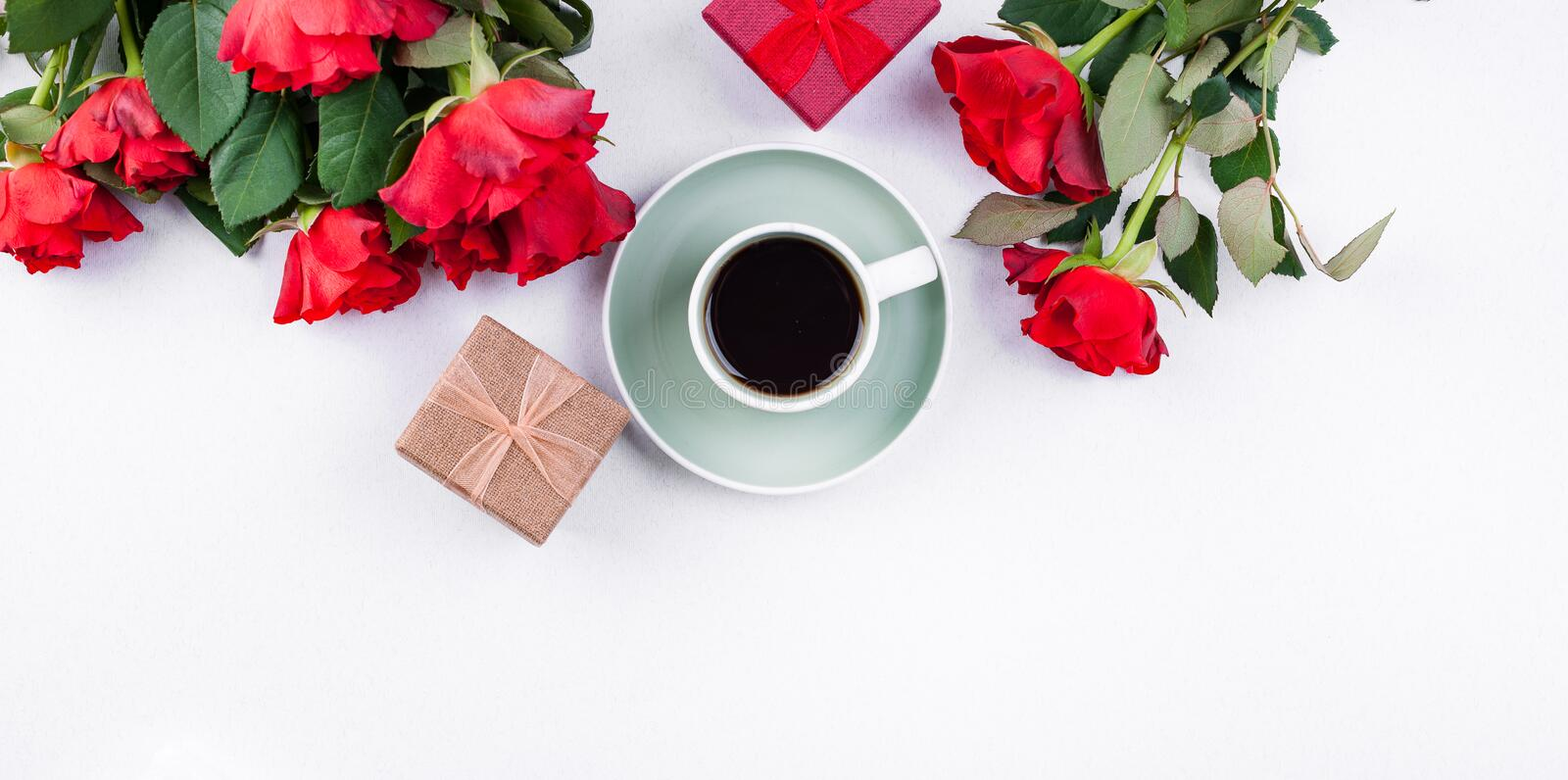 A bouquet of red roses and fresh aromatic tea for a romantic breakfast. Flowers and a letter as a gift. Valentine`s day and mothe royalty free stock image