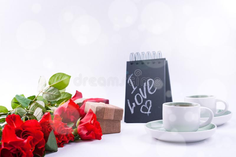 A bouquet of red roses and fresh aromatic tea for a romantic breakfast. Words of love on a note and a gift with flowers. Valentine stock image