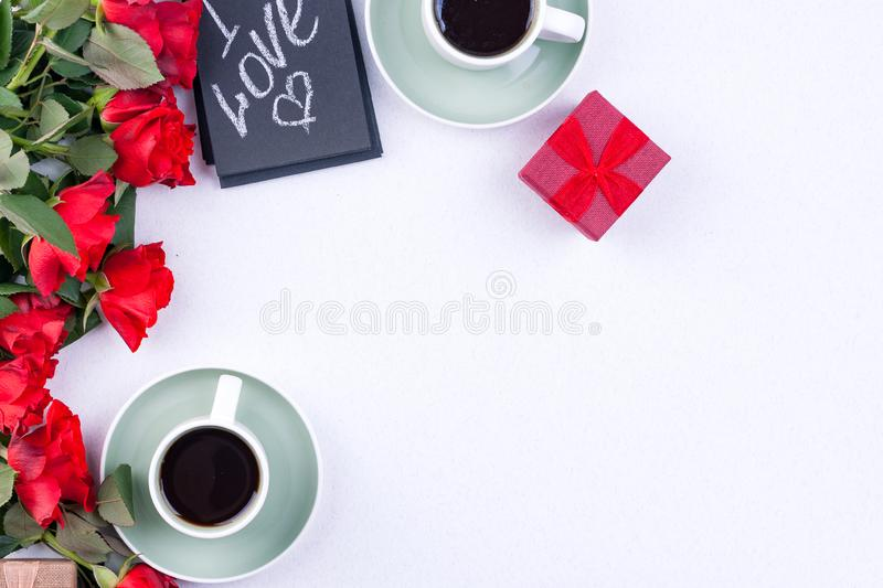 A bouquet of red roses and fresh aromatic tea for a romantic breakfast. Words of love on a note and a gift with flowers. Valentine stock photos