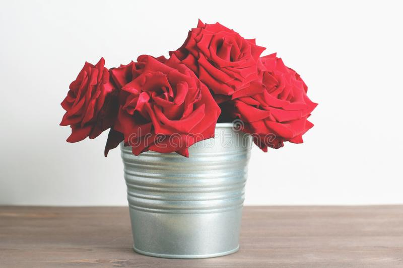 Bouquet of red roses in galvanized bucket on dark wooden table. retro filter stock photo