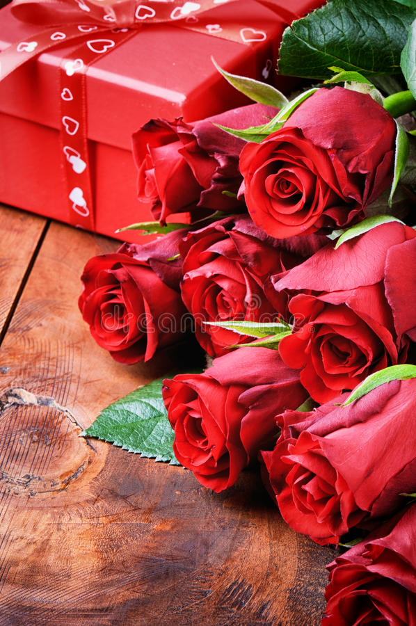 Bouquet of red roses and gift box. On wooden table stock images