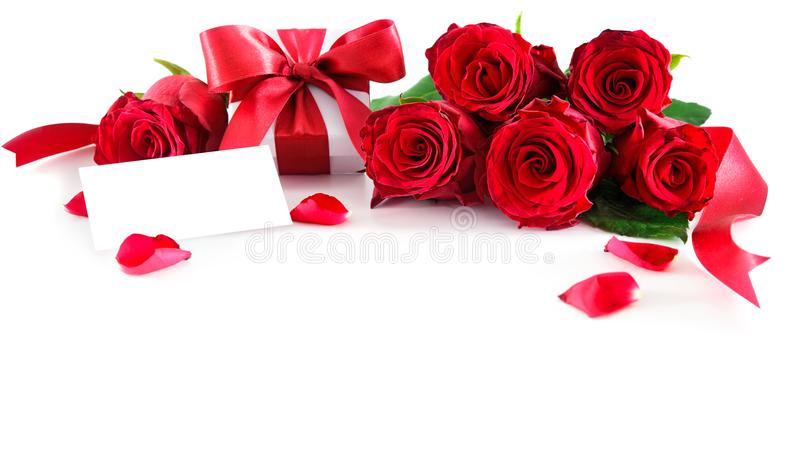 Bouquet of red roses and gift box with empty tag. Isolated on white background. Valentine`s Day, Mother`s Day, Happy Birthday, Anniversary, Wedding concept stock photography