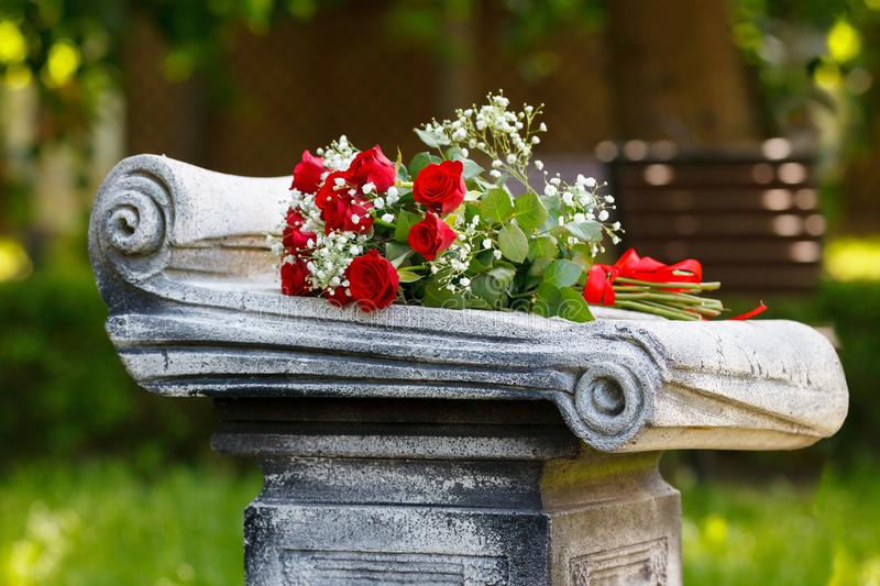 Bouquet of red roses on a gravestone in the cemetery stock images