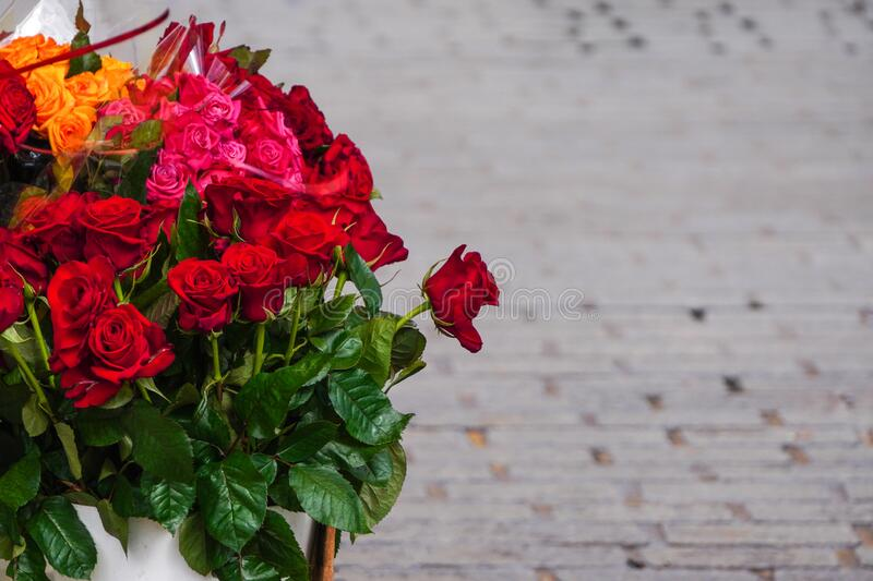 A bouquet of red roses on grey background. Selling flowers on the street. Red flowers in the water. A bouquet of red roses on grey background. Selling flowers on royalty free stock photography