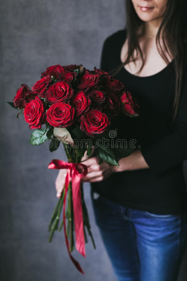 Bouquet of red roses in the hands of a woman stock photo