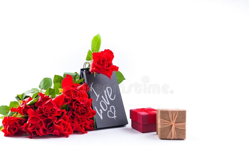 A bouquet of red roses and a letter with the text of love. Gift and flowers on a white background. The concept of Valentine`s Day royalty free stock image