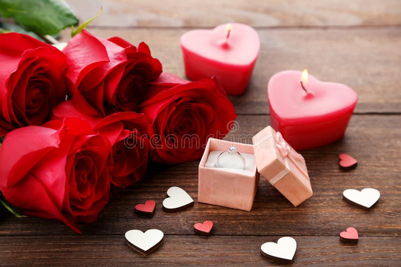 Red roses with silver ring. Bouquet of red roses with silver ring and candles on wooden table royalty free stock photography