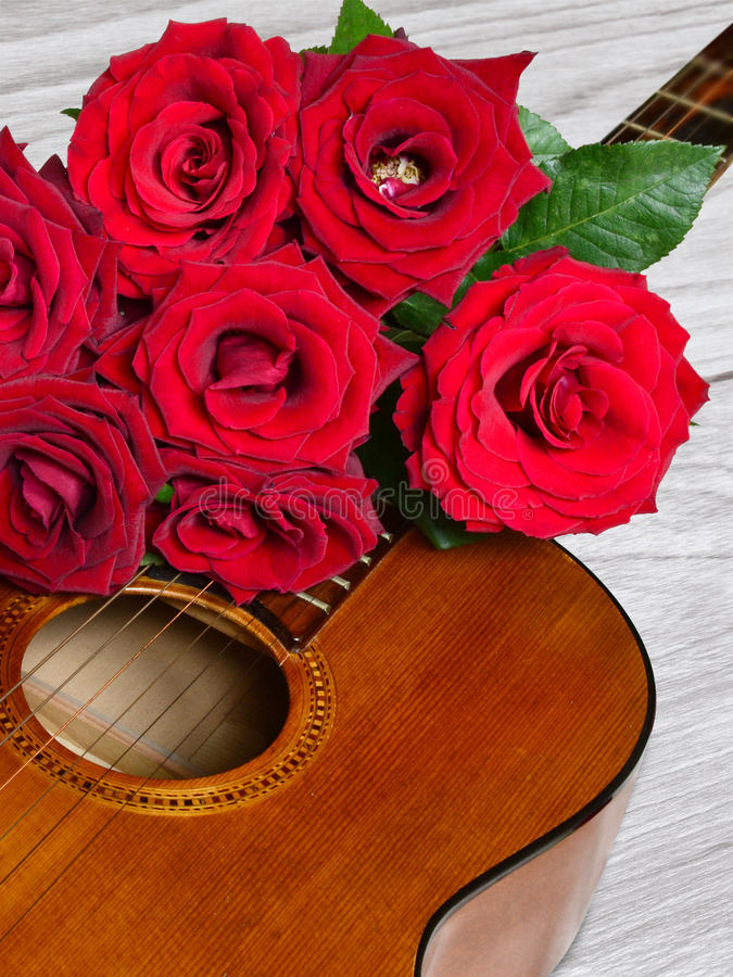 Bouquet of red roses on top of classical guitar stock photography