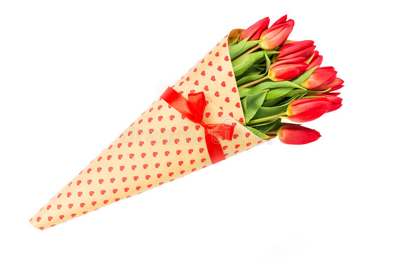Bouquet of red spring tulips wrapped in paper with hearts. Isolated over white. Background stock photos