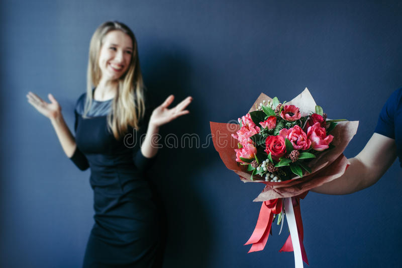 Bouquet of red tulips as boyfriend`s gift for cute girl. royalty free stock photos