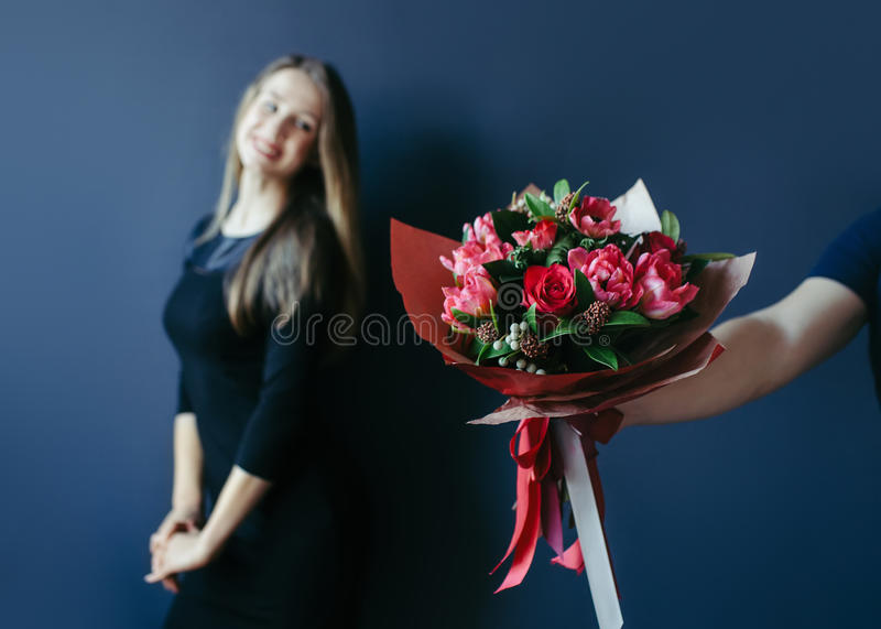 Bouquet of red tulips as boyfriend`s gift for cute girl. royalty free stock images