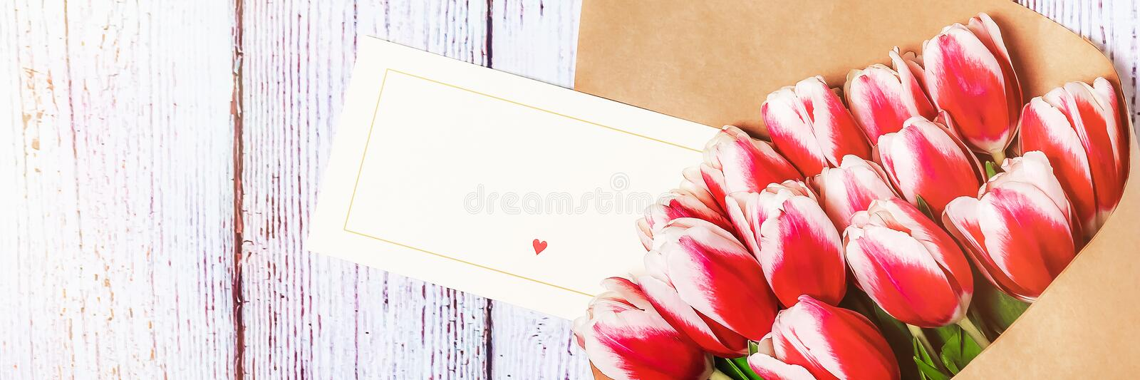 Bouquet of red tulips on the background of old, wooden boards. Place for text.  stock image