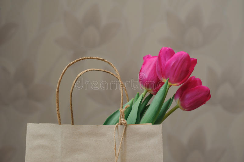 Bouquet of red tulips in paper bag stock photography