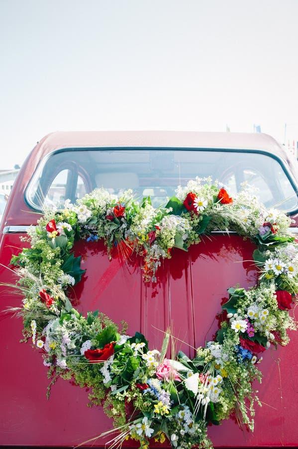 Bouquet on a red wedding car