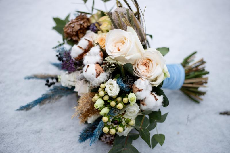 Bouquet of roses and cotton flowers in the snow royalty free stock photo