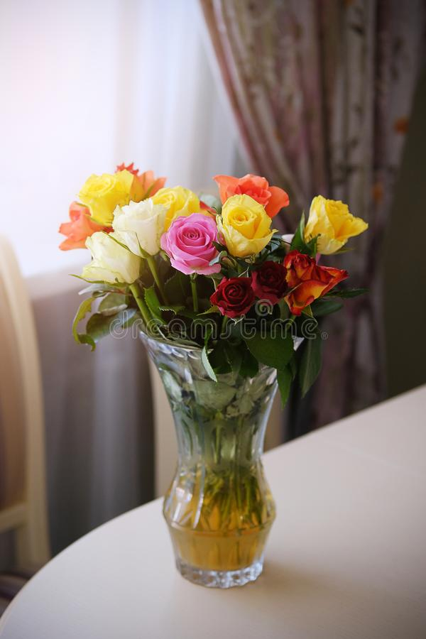 Bouquet of roses of different colors on the edge of a wooden table. Flower arrangement in a transparent glass vase. Modern kitchen stock images