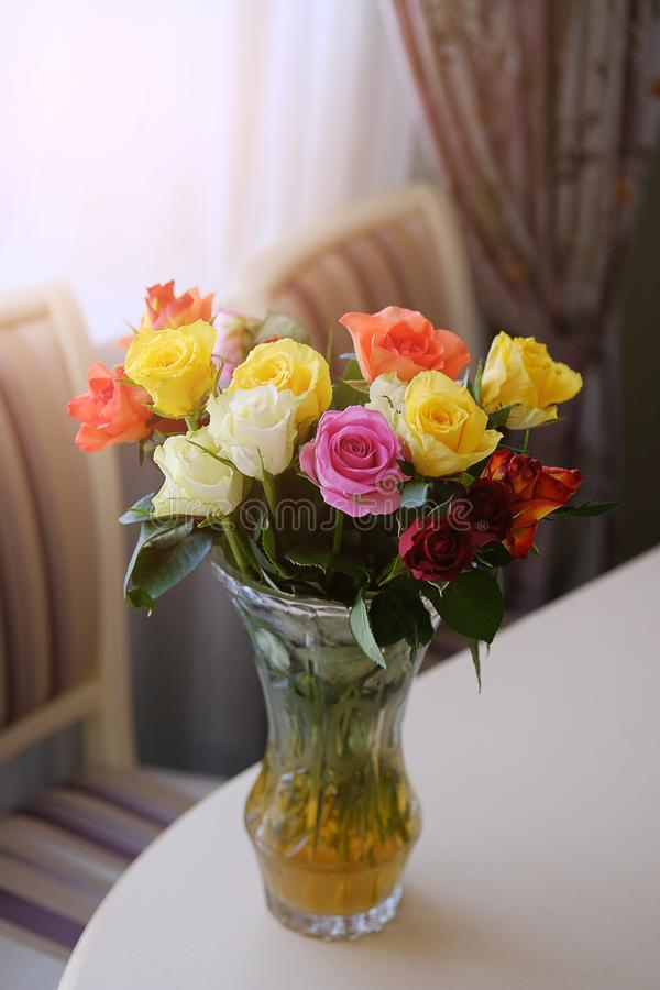 Bouquet of roses of different colors on the edge of a wooden table. Flower arrangement in a transparent glass vase. Modern kitchen stock photography