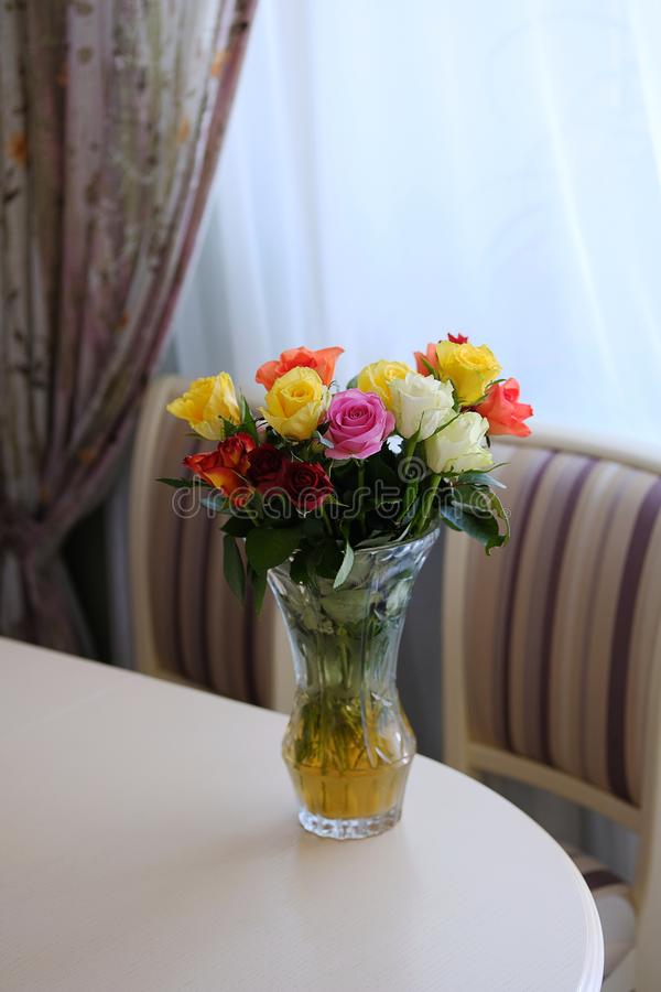 Bouquet of roses of different colors on a light table. Flower arrangement in a transparent glass vase. Modern kitchen interior royalty free stock photo