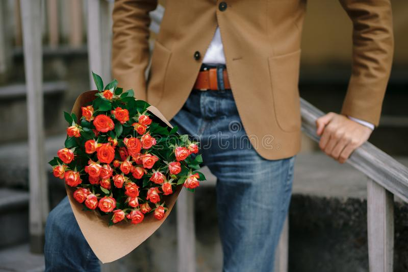 A bouquet of roses in male hands. A bouquet of flowers in male hands. Focus on fresh roses folded in craft paper in a stylish man arms, wearing jeans and wool royalty free stock photography