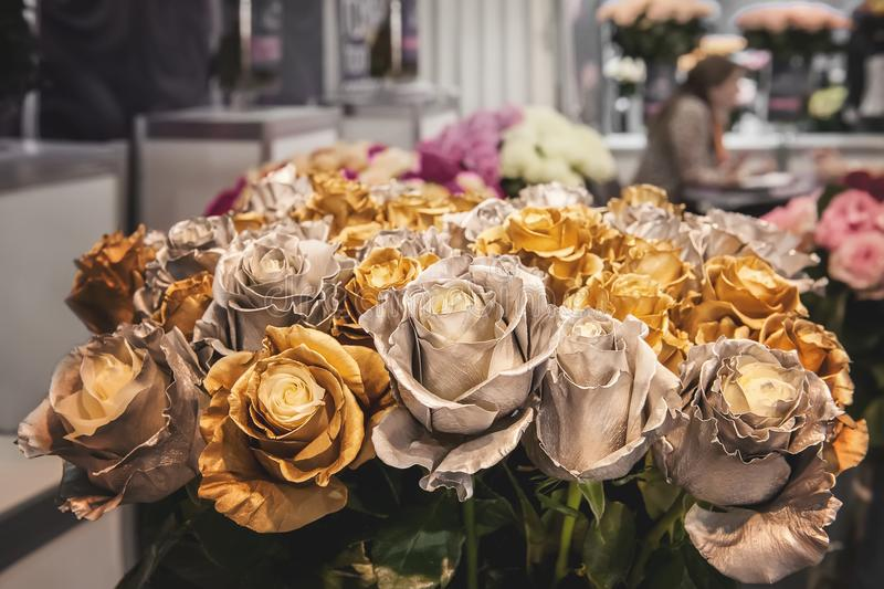 Bouquet of roses metallic color. Chameleon flowers with gold and silver petals on the edges. royalty free stock photography