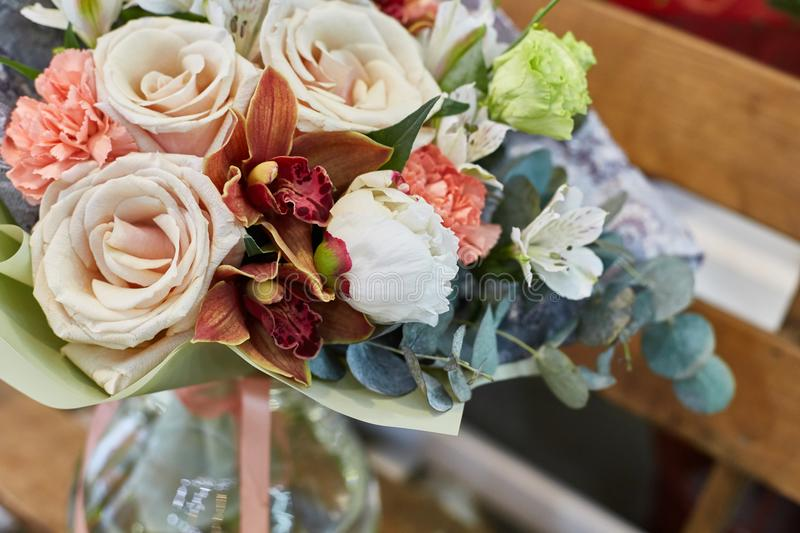 A bouquet of flowers in a glass vase on a background of wooden boards in a warm brown scale. stock photos