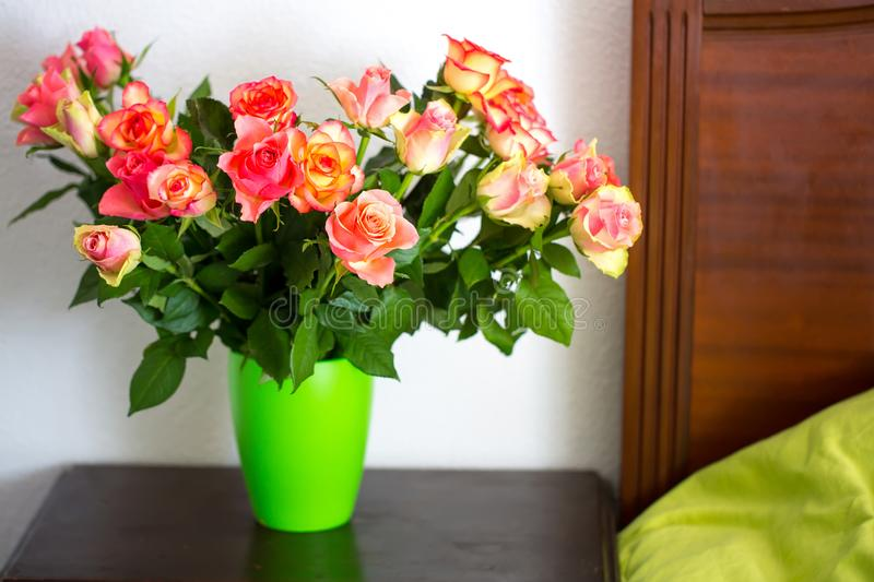 A bouquet of roses in a vase on a bedside table. A bouquet of roses in a green vase on a bedside table royalty free stock photos