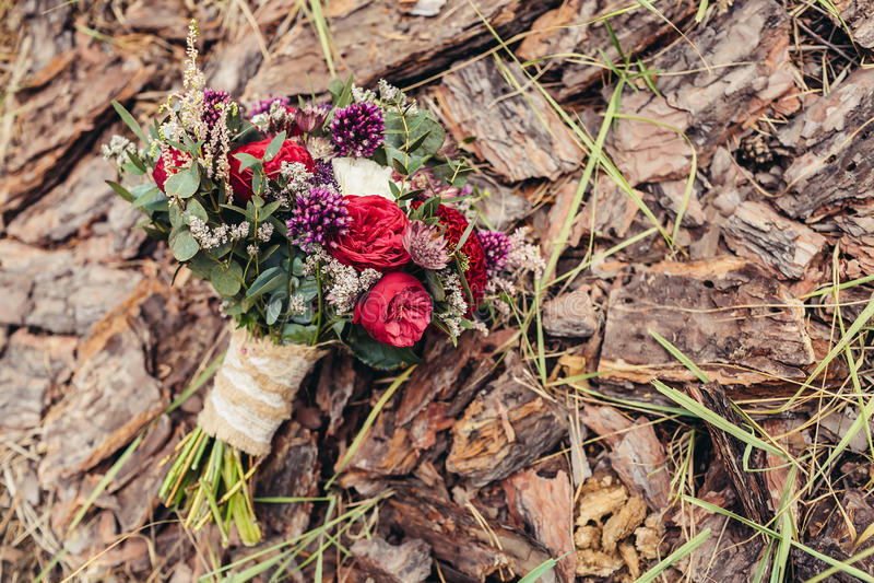 Bouquet rustique de mariage avec les roses rouges et lilas sur le backgrou d'écorce image libre de droits