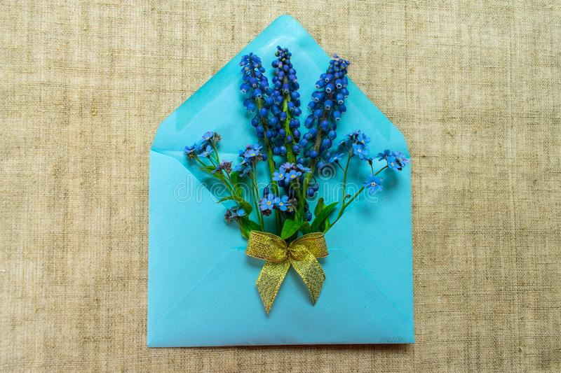 A bouquet of small blue flowers in a blue envelope decorated with a golden bow on a tablecloth made of natural flax. stock photography