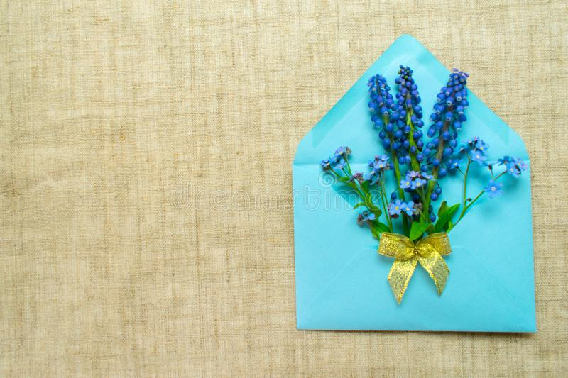 A bouquet of small blue flowers in a blue envelope decorated with a golden bow on a tablecloth made of natural flax. stock image