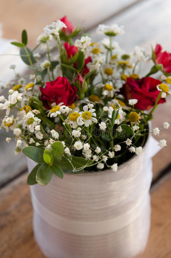 Bouquet of small flowers arranged in a white tin vase stock photo