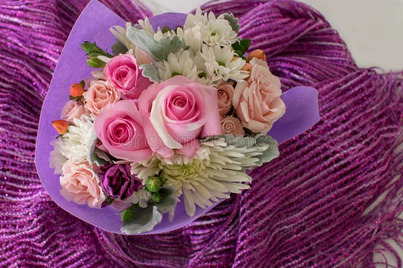 Bouquet of small roses and other mixed flowers on purple fabric. royalty free stock image